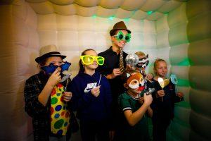 Gasten maken gebruik van de photobooth Het Fotohuisje en maken daarbij gebruik van de grappige props (attributen) zoals gekke brilletjes en maskers